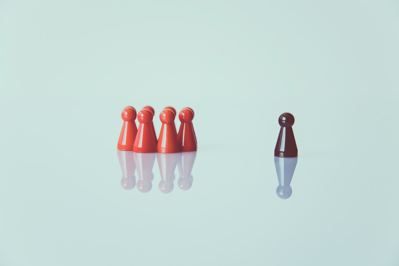Pawns on a table, one standing out