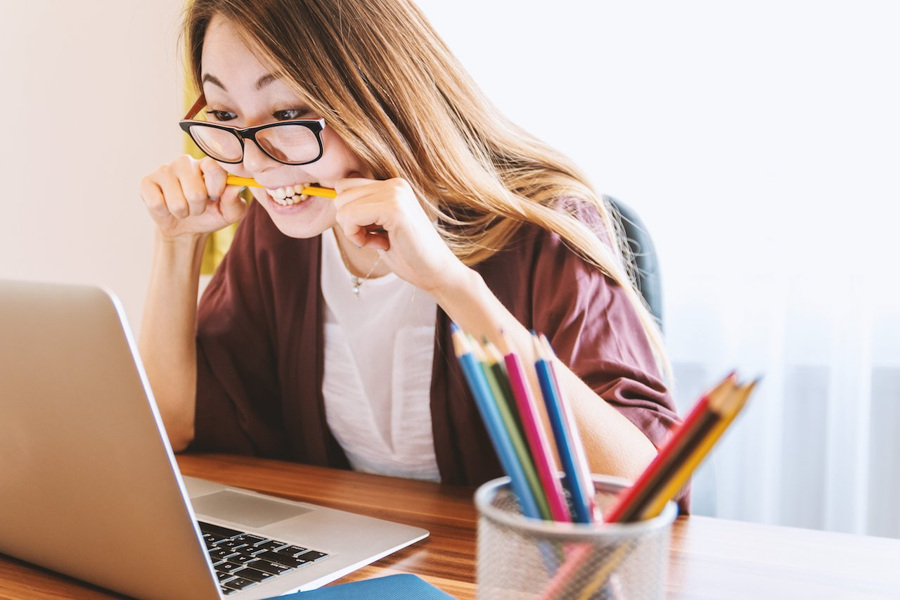 Woman sitting at laptop chewing pencil in frustration