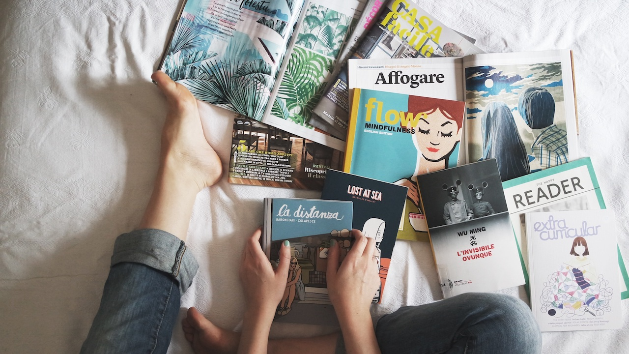 Sitting with a pile of magazines on a bed