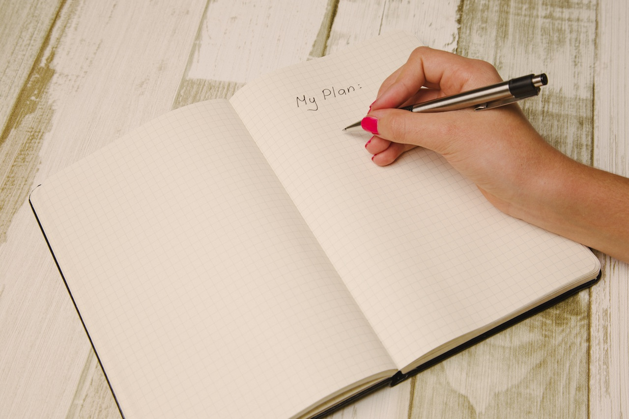 Female hand writing My Plan in a notebook with a pen