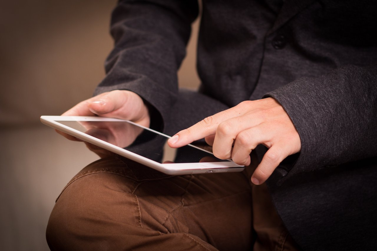 Man operating tablet while sitting down