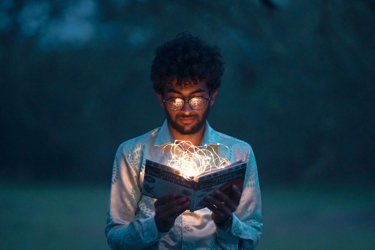 Man reading a book outside, with tangled light shining from it