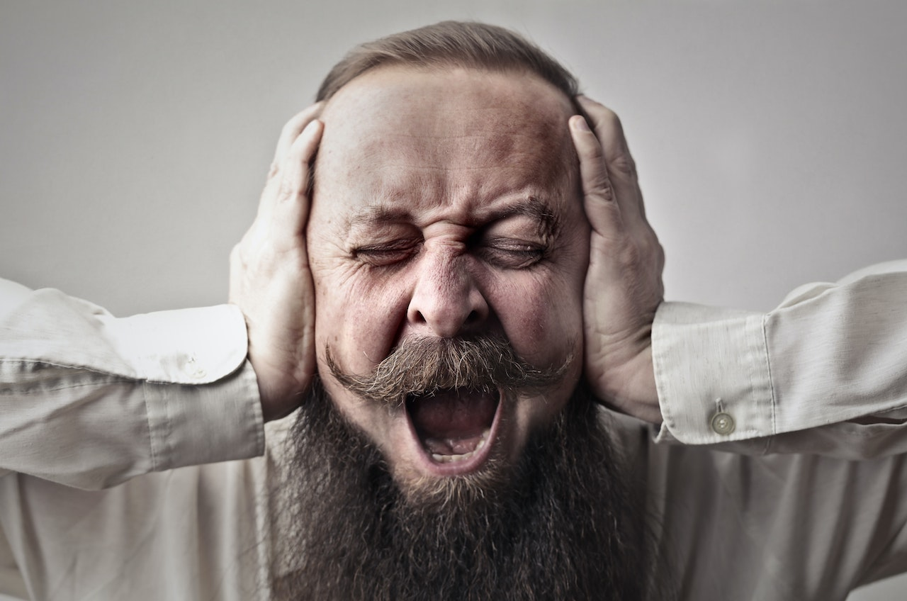 Man screaming, covering his ears